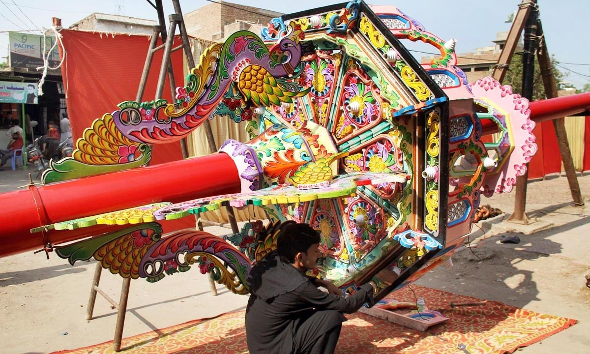 A man is seen busy in giving final touches to the decoration work of an Alam before re-installation. -Online