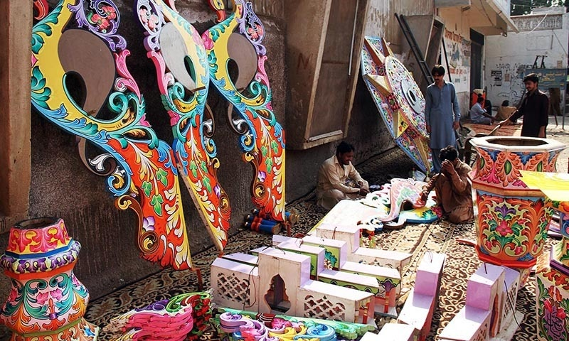 Men seen busy in giving final touches to decoration work of an Alam before re-installation in Hyderabad. — Online