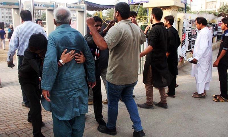 Volunteers frisking mourners due to security concerns during the first Majlis in Karachi. —Online