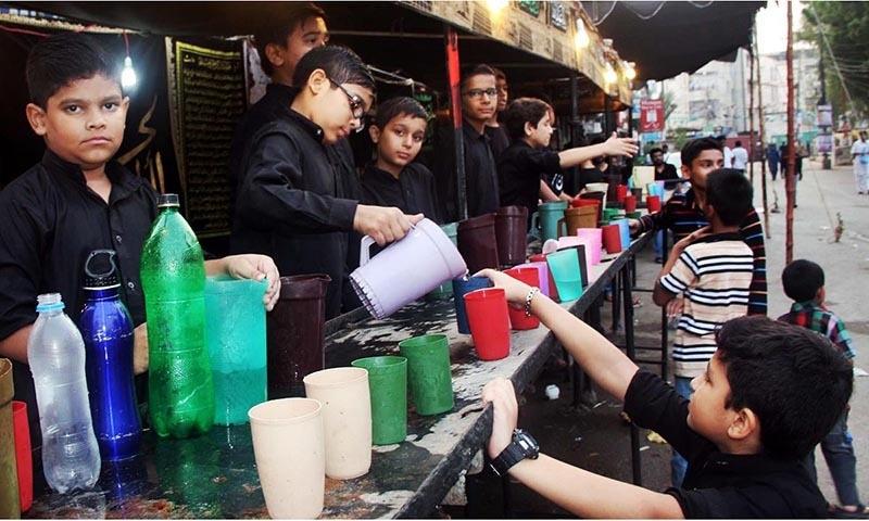 Children seen distributing water at  a Sabeel at Soldier Bazaar in Karachi. -Online