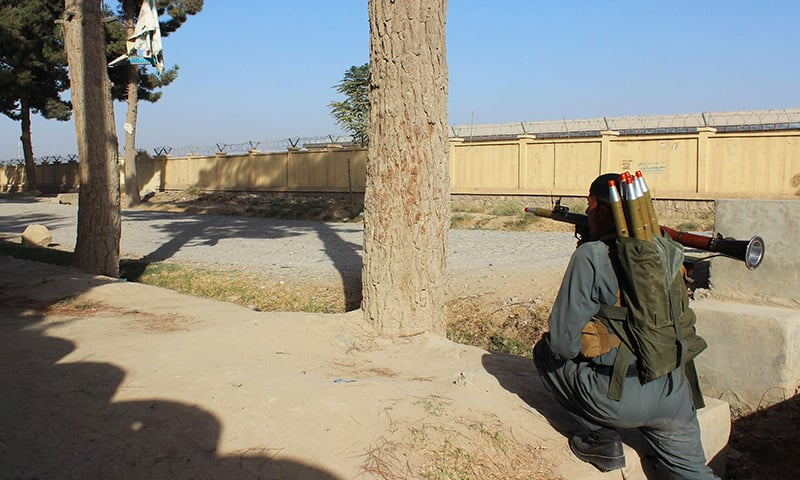 An Afghan policeman takes position during fighting between Taliban militants and Afghan security forces in Kunduz . -AFP