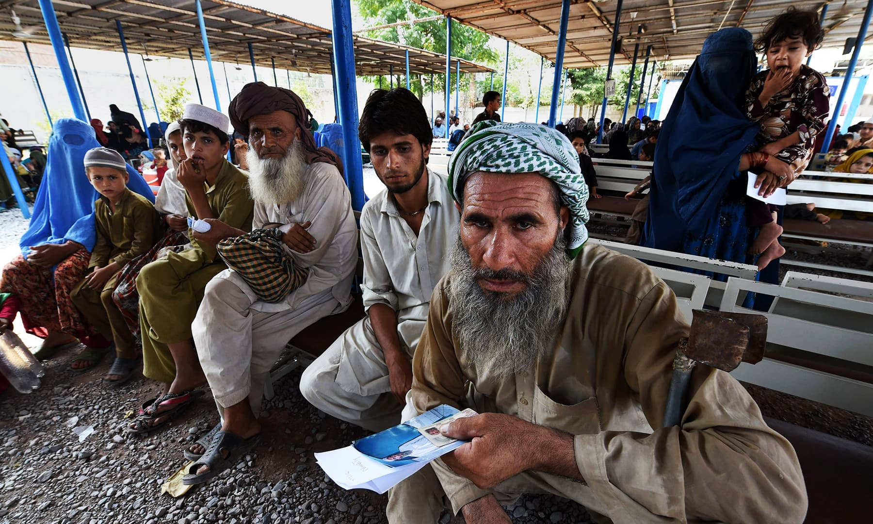 Afghan refugees wait to register at the UNHCR repatriation centre on the outskirts of Peshawar. — AFP