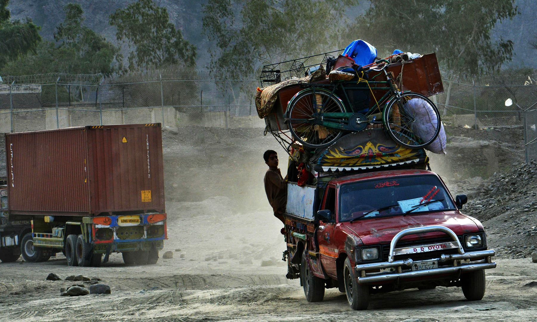 Afghan refugees travelling in a loaded vehicle as they arrive to cross the border into Afghanistan, at the Torkham crossing point in Pakistan's tribal Khyber district. — AFP