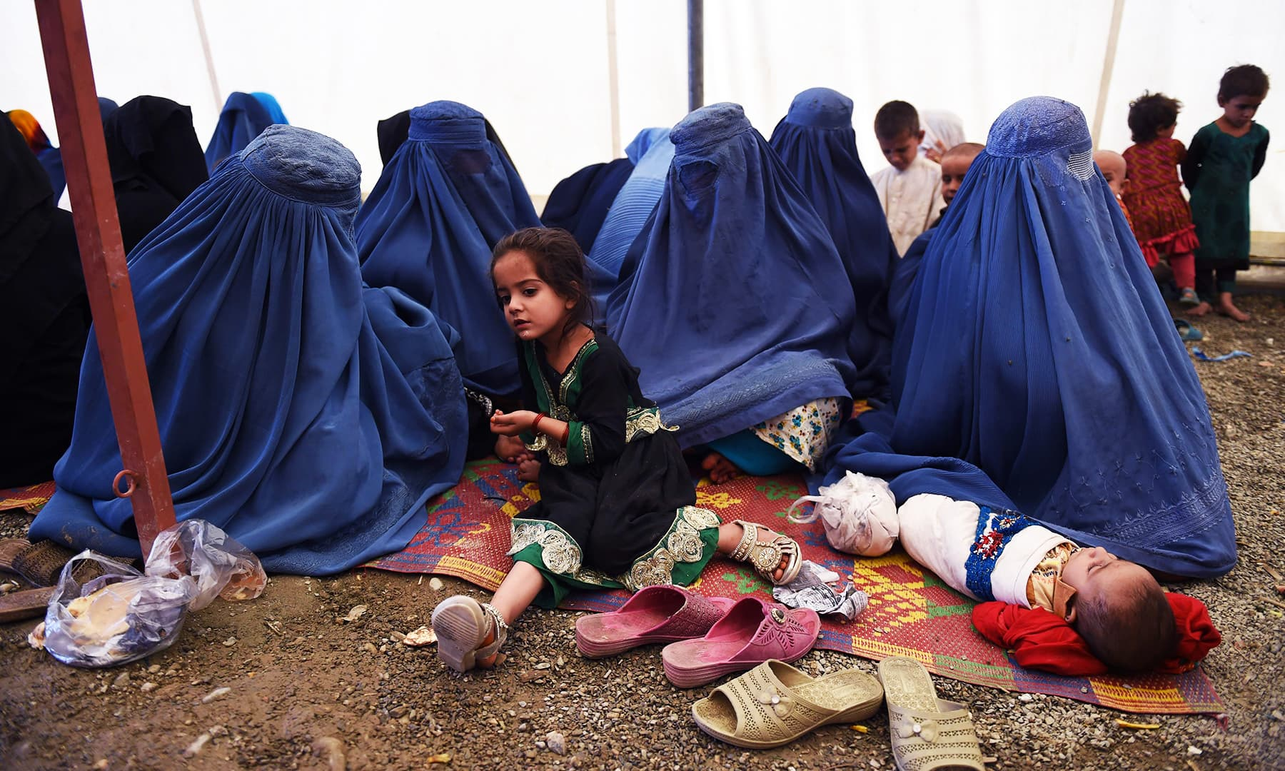 Afghan refugee women sit with their children after returning to Afghanistan from Pakistan, at the UNHCR camp on the outskirts of Kabul. — AFP