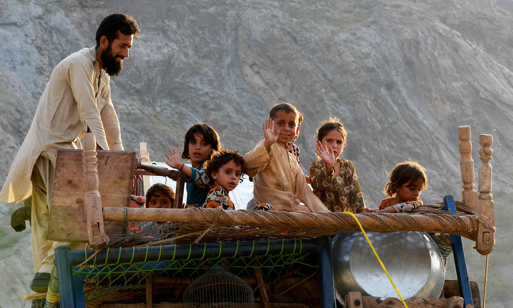 A repatriated Afghan refugee family travel on a loaded vehicle as they prepare to cross the border into Afghanistan, at the Torkham crossing point in Pakistan's tribal Khyber district. — AFP