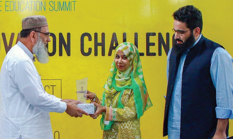 Secretary Science and Information Technology Mohammad Salim gives away award to a participant of the Education Innovation Challenge in Peshawar on Wednesday. — Dawn