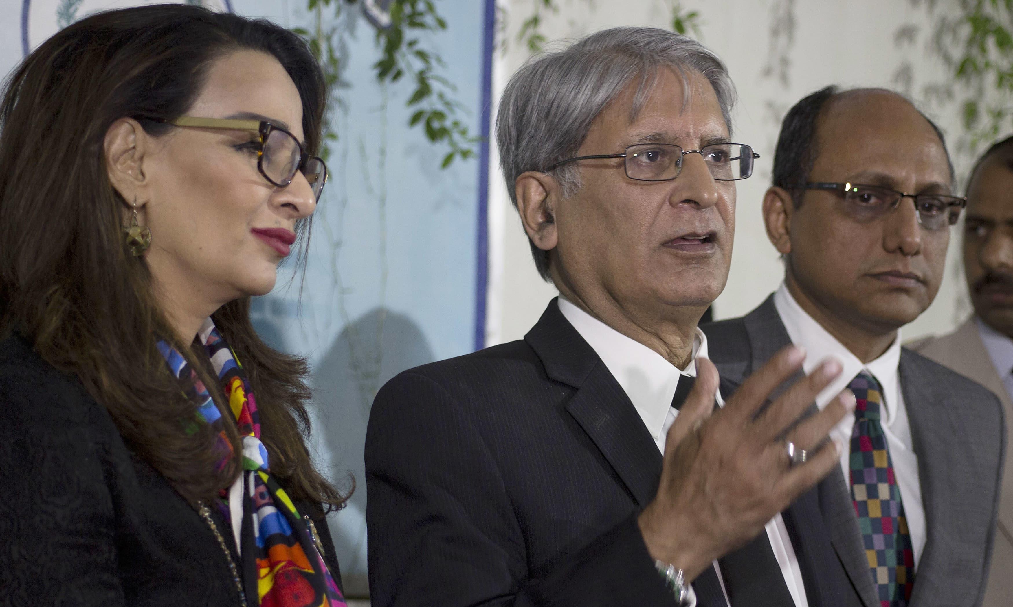 Aitzaz Ahsan addresses media outside the Parliament. —AP