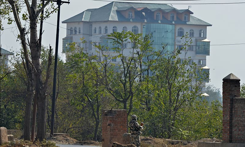 An Indian paramilitary trooper looks towards a building where suspected rebels are thought to be hiding. ─ AFP