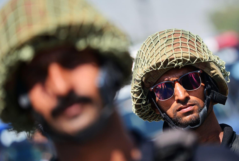 Policemen escort a procession in Karachi on Muharram 8. ─ AFP