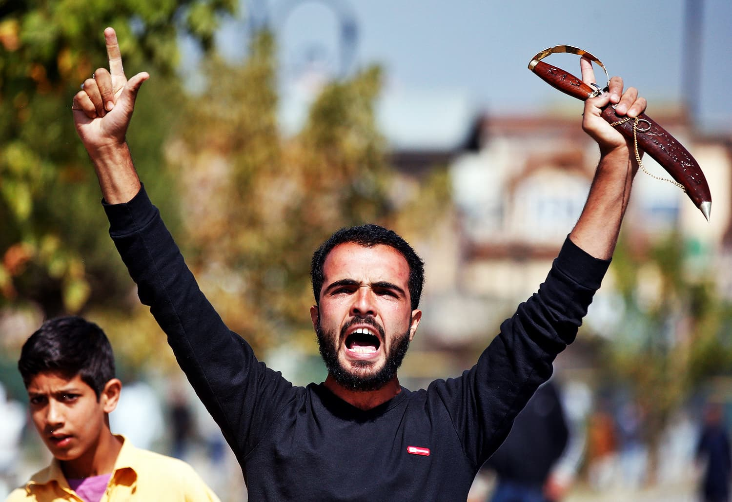 A Kashmiri mourner shouts slogans as Indian policemen attempt to stop a Muharram procession during a curfew in downtown Srinagar. ─ Reuters
