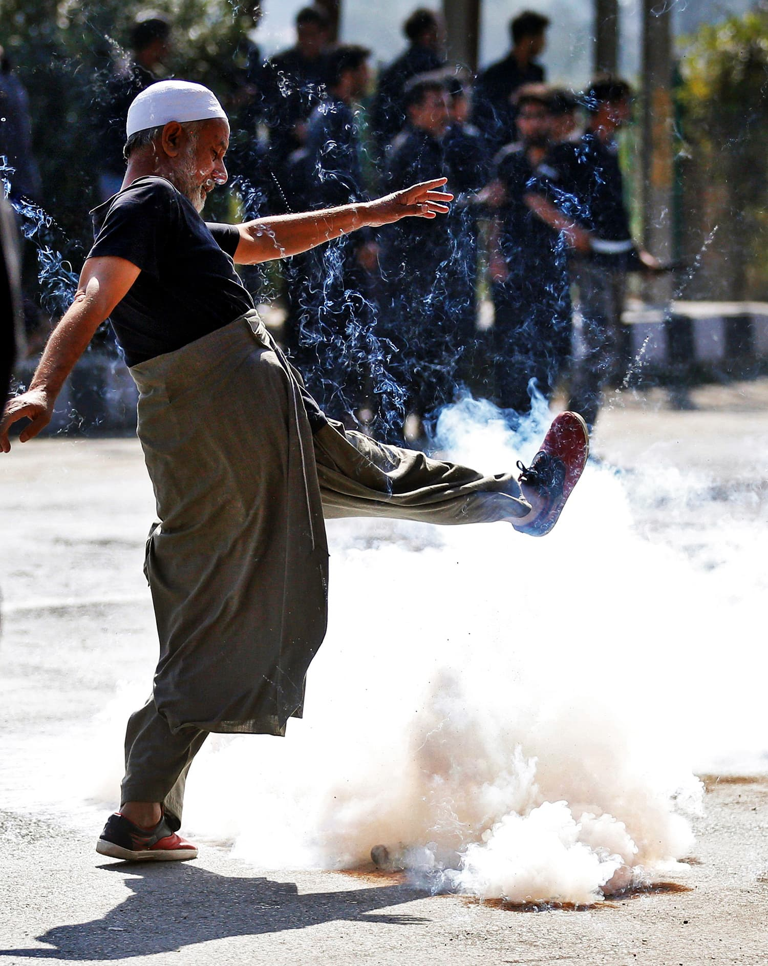 A Kashmiri man kicks a tear gas shell fired by Indian policemen to disperse the mourners as they try to participate in a Muharram procession during a curfew in downtown Srinagar. ─ Reuters