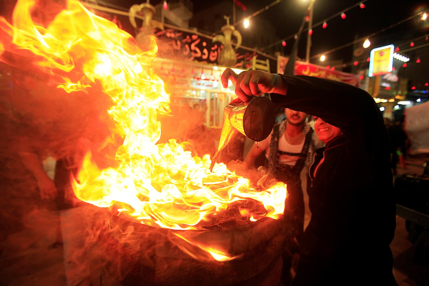 Mourners perform with fire during commemorations for Ashura in Najaf, Iraq. ─ Reuters
