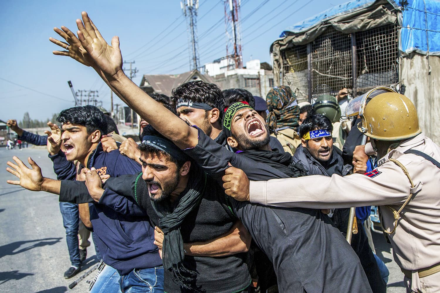 Kashmiri mourners shout religious and pro-freedom slogans as Indian policemen stop them from participating in a Muharram procession during curfew in Srinagar. ─ AP