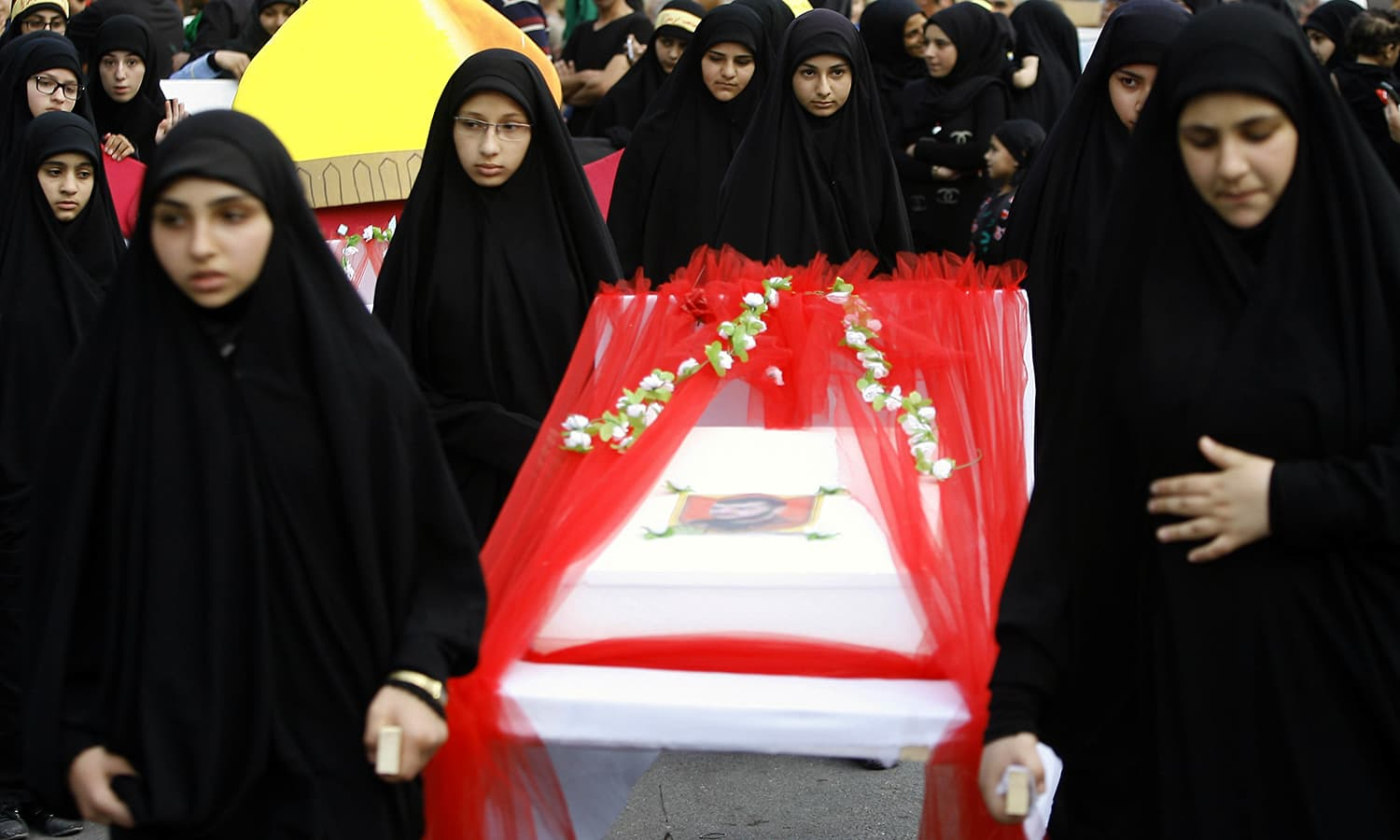 Girls carry a mock coffin to remember Hezbollah fighters killed in Syria during a rally to mark the seventh day of Ashoura in the southern village of Seksakiyeh, Lebanon. ─ AP
