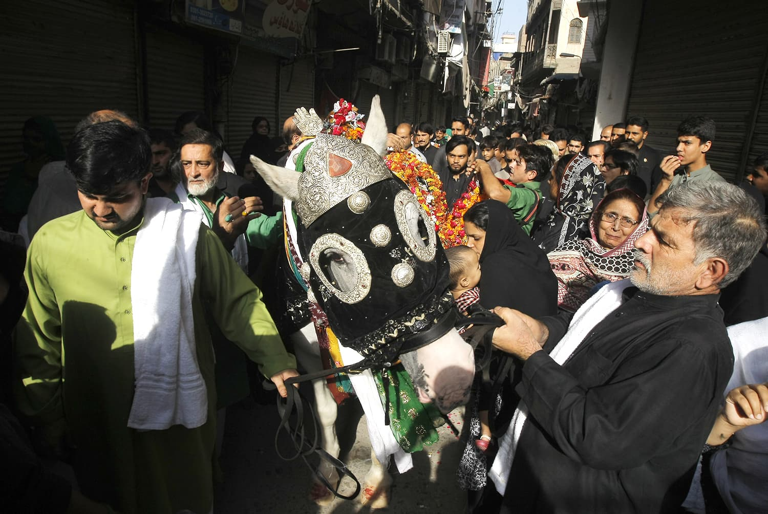 Mourners pay respects to Zul-Jinnah, a horse symbolising the horse Hazrat Imam Hussain (RA) used to fight against his enemy in Karbala. ─ AP