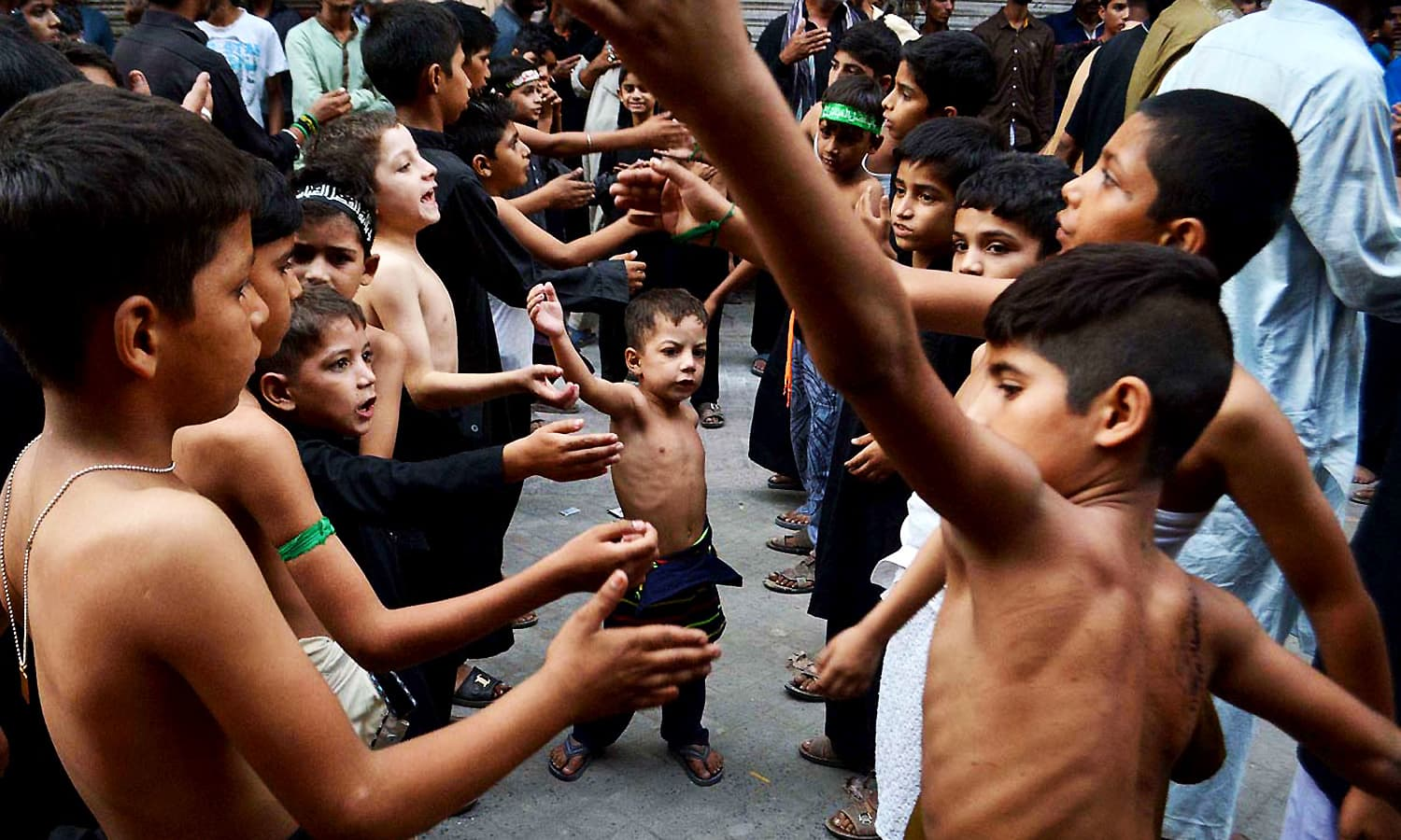 Children attending a Muharram procession at Anarkali market in Lahore. ─ APP