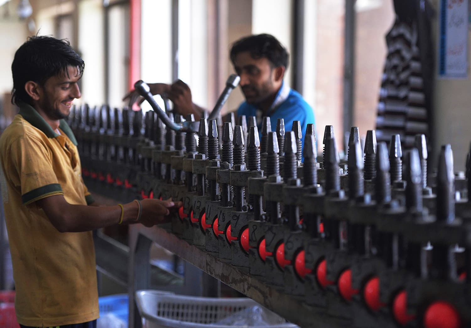A Pakistani worker shapes pink cricket balls in a molding machine at the Grays of Cambridge factory in Sialkot.—AFP