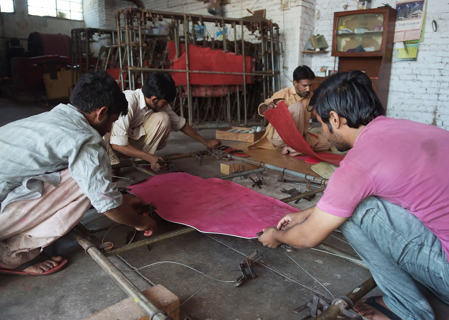 Pakistani workers fix leather for pink cricket balls in a frame at the Grays of Cambridge factory in Sialkot. —AFP