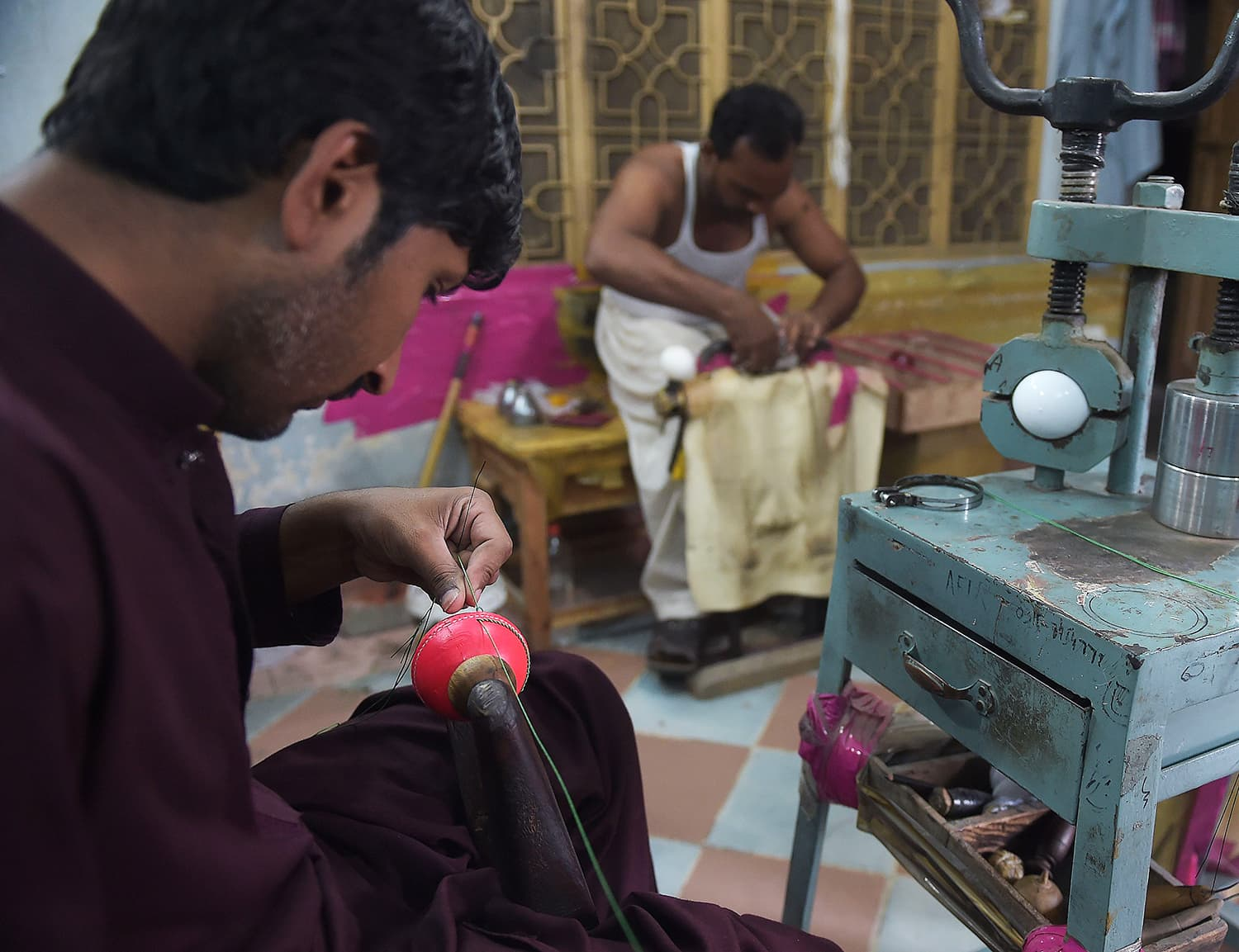 A Pakistani worker stitches a pink cricket ball at the Malik Sports factory in Sialkot. —AFP