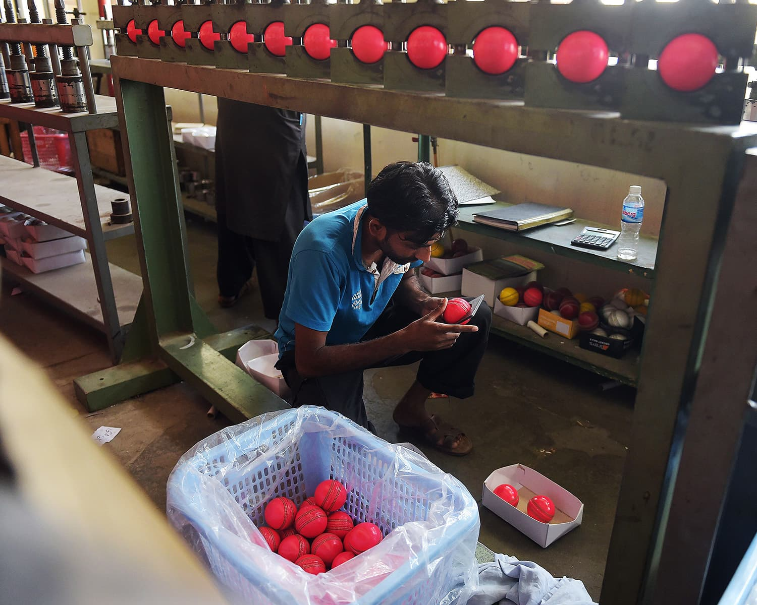 A Pakistani worker measures pink cricket balls  at the Grays of Cambridge factory in Sialkot.—AFP