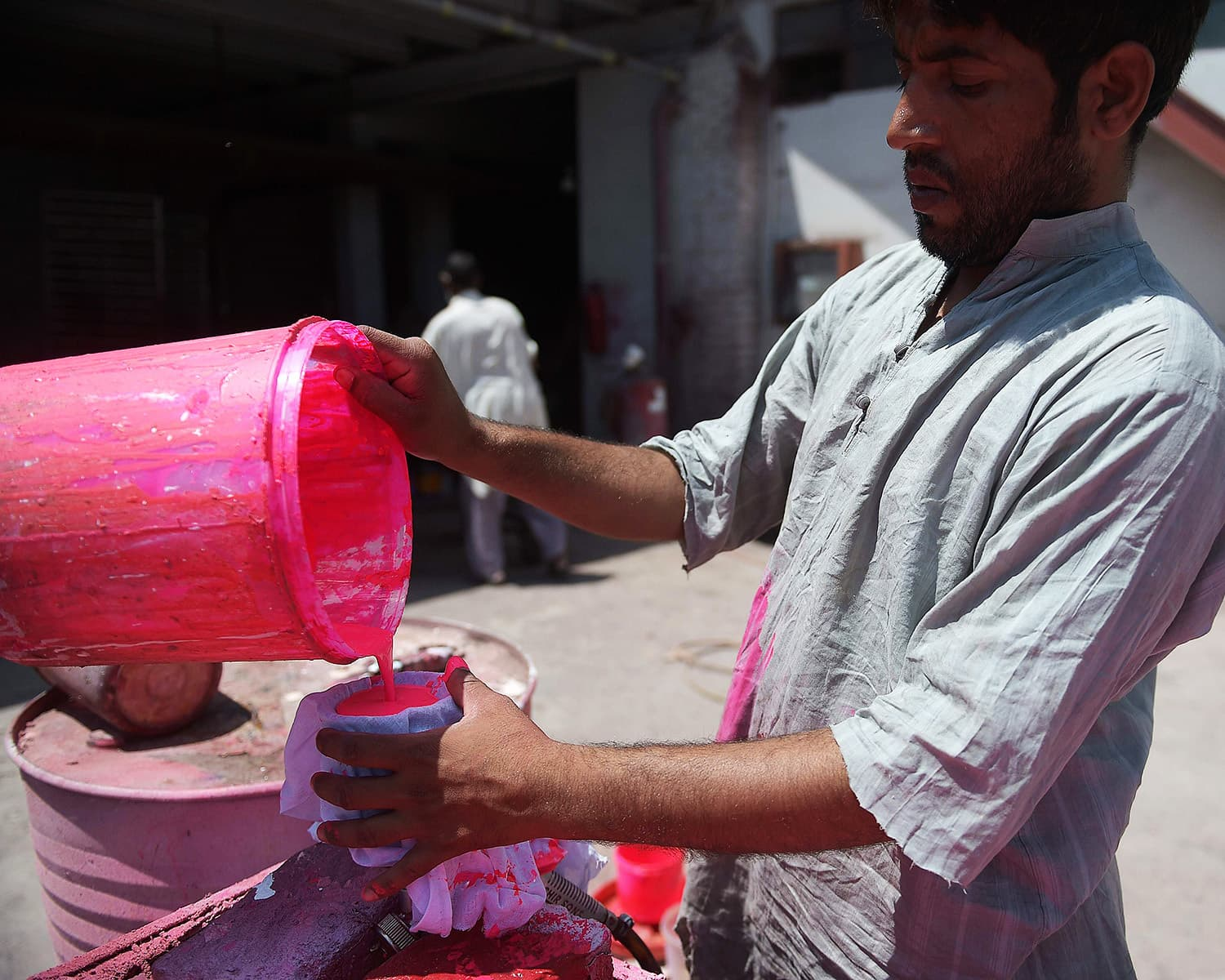 A Pakistani worker prepares the pink dye for pink cricket balls at the Grays of Cambridge factory in Sialkot.—AFP