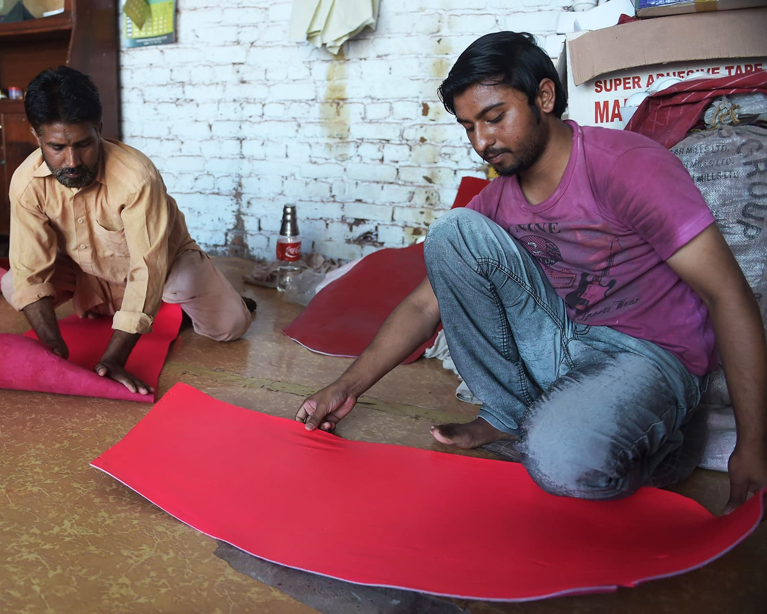 Pakistani workers prepare leather for pink cricket balls at the Grays of Cambridge factory in Sialkot.—AFP