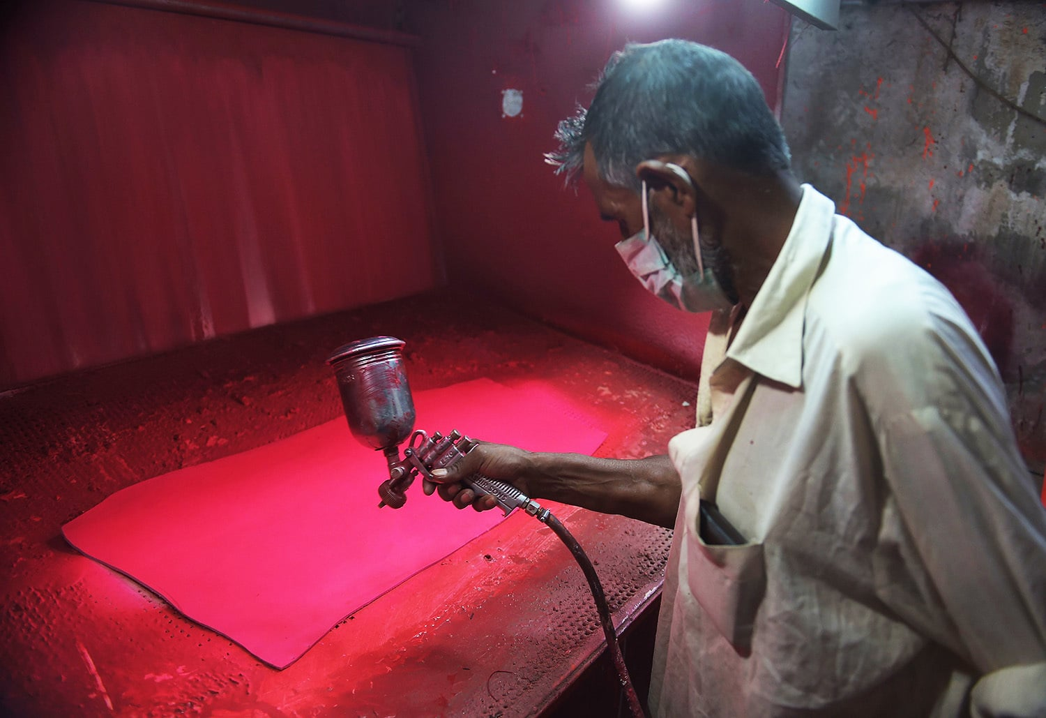 Pakistani workers sprays colour onto leather for pink cricket balls at the Grays of Cambridge factory in Sialkot.—AFP