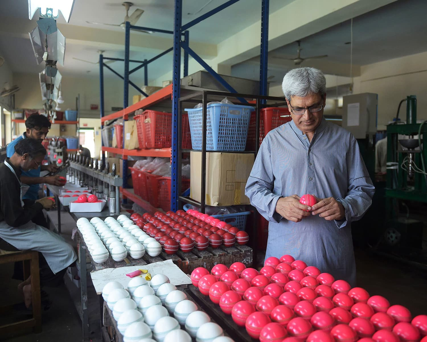 Chief Executive of 'Grays of Cambridge', Khawar Anwar Khawaja inspects a pink cricket ball at the factory in Sialkot. —AFP