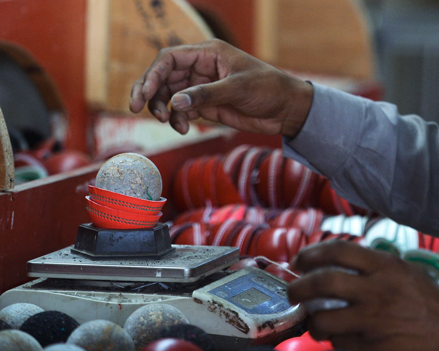 A Pakistani worker weighs the components of a pink cricket ball before stitching at the Grays of Cambridge factory in Sialkot. —AFP
