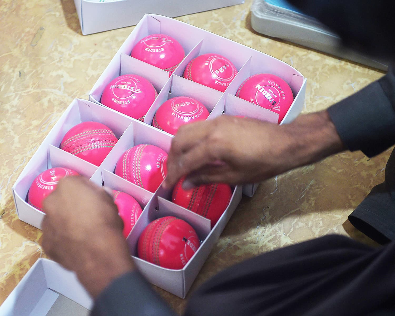 A Pakistani worker packs pink cricket balls into boxes at the Grays of Cambridge factory in Sialkot.—AFP/File