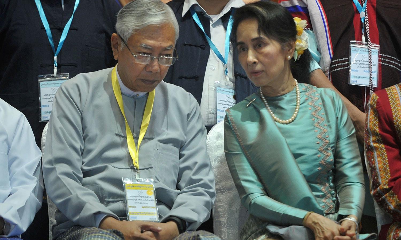 میانمار کے وزیراعظم ہٹن کیوا اور ریاستی کونسلر آنگ سان سو ملک میں ہونے والے جنگ بندی کے ایک سال مکمل ہونے پر منعقدہ ایک تقریب میں موجود ہیں — فوٹو: اے ایف پی