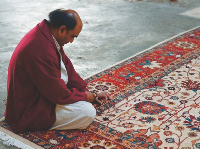 A weaver looking at a finished carpet. There is a need to develop carpet clusters in the places where carpets are made. Exporters need to develop such clusters hosting a few hundreds of looms at a specified place.—AFP