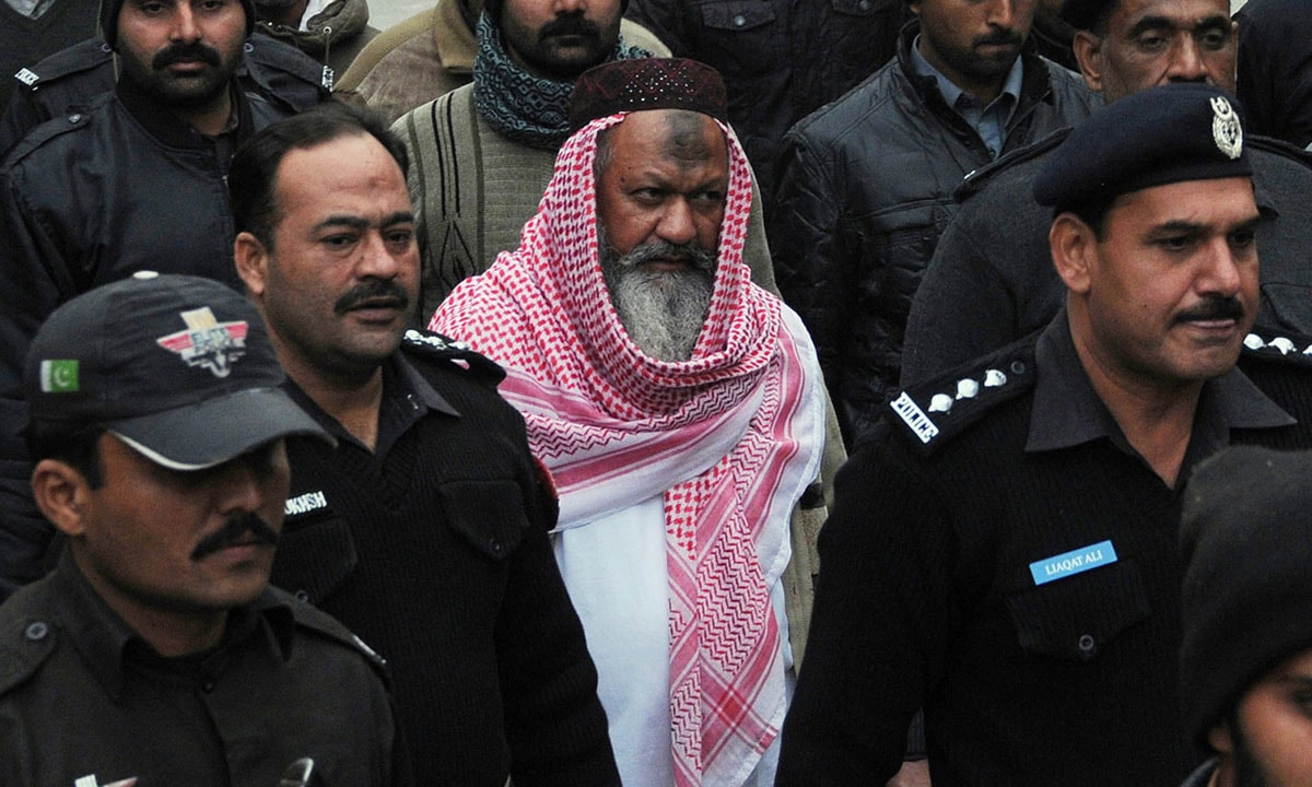 Policemen escort Malik Ishaq, the head of the banned militant outfit Lashkar-e-Jhangvi, in December 2014 | AFP