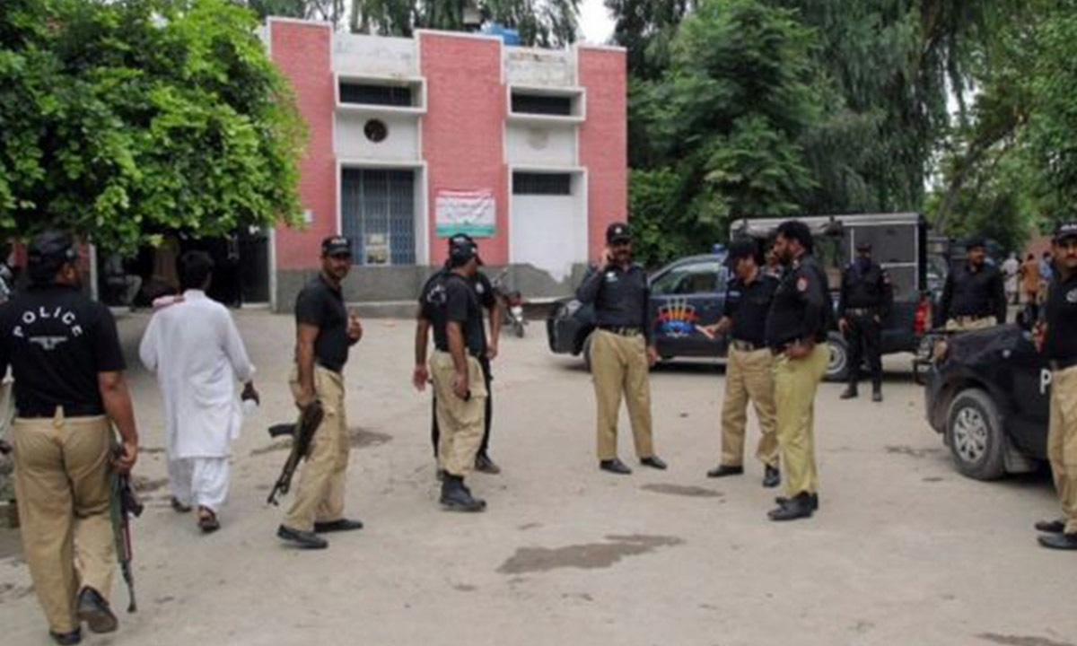 Policemen stand outside the hospital where Malik Ishaq's body was brought after his death | AFP