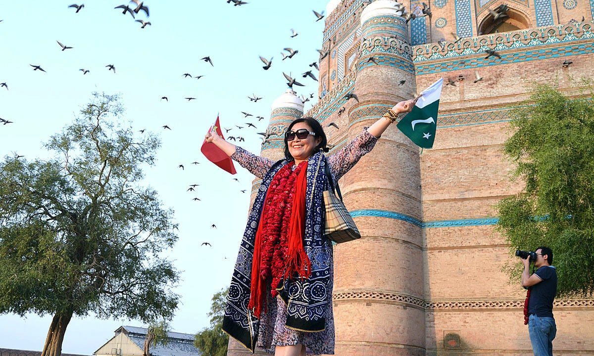 Participant of Pak-China Friendship Car Rally poses while carrying flags of China and Pakistan. —APP