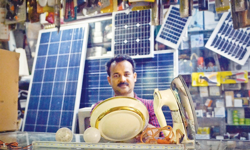 A shopkeeper in Saddar's Regal Market proudly displays monocrystalline and polysilicone solar panels. Prices tend to vary by type and size