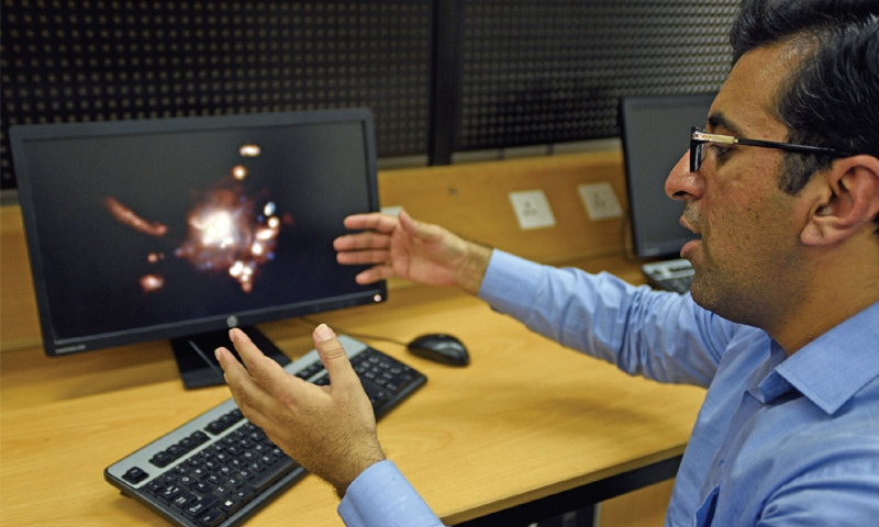 Dr Fazeel Mehmood Khan connects the telescope to a computer, to capture images of a galaxy.