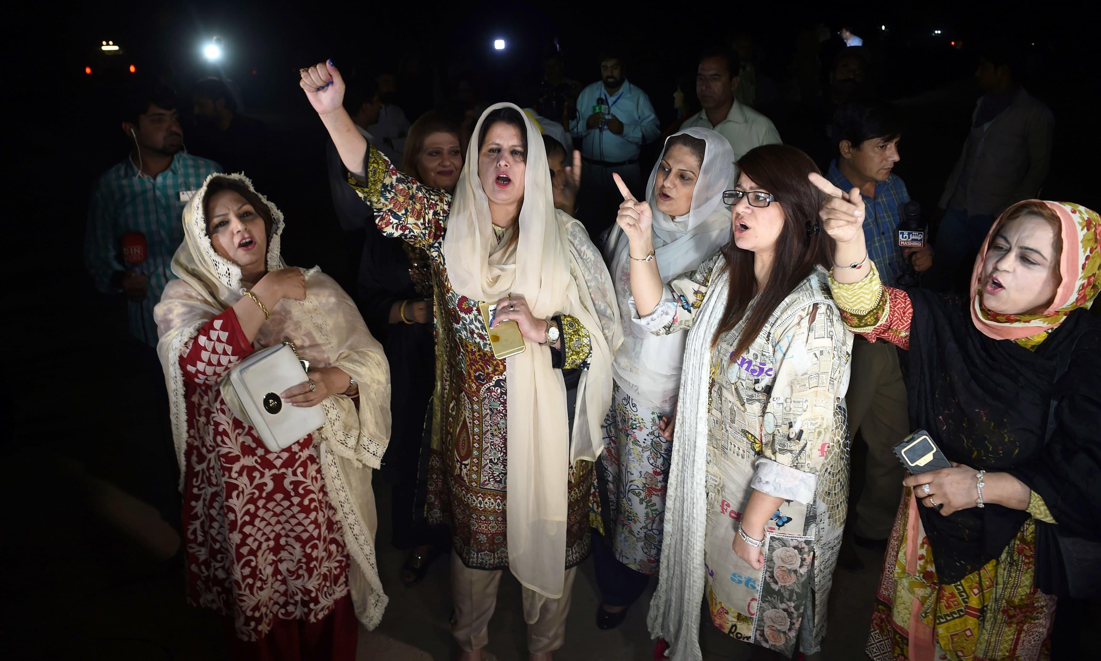 PTI 's women activists shout slogans. —AFP