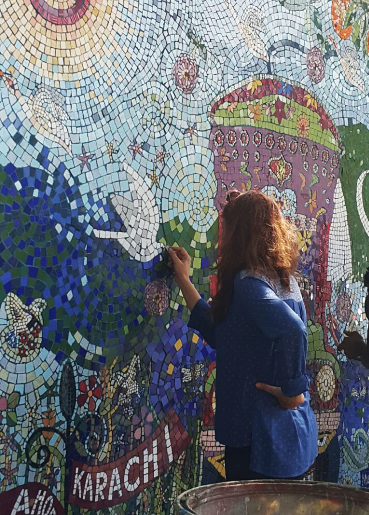 The artist adding the final touches to the mosaic. Muna Siddiqui.