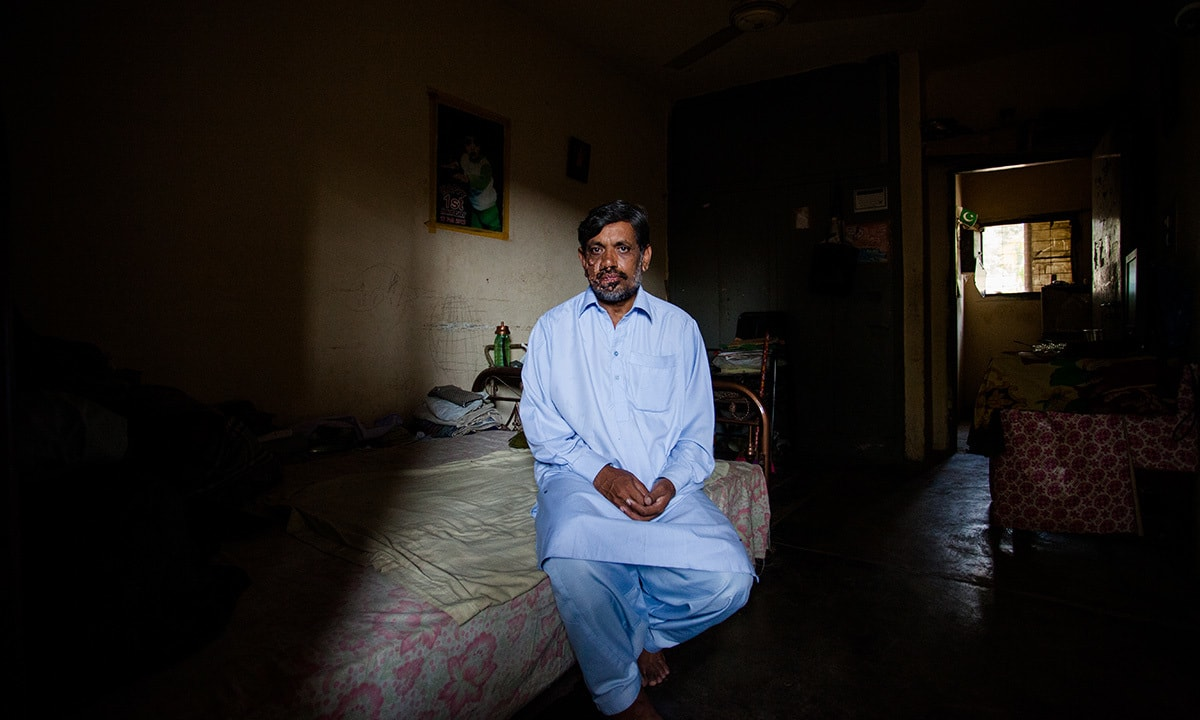 An employee sits in his two bedroom house inside Karachi Steel Mill Township