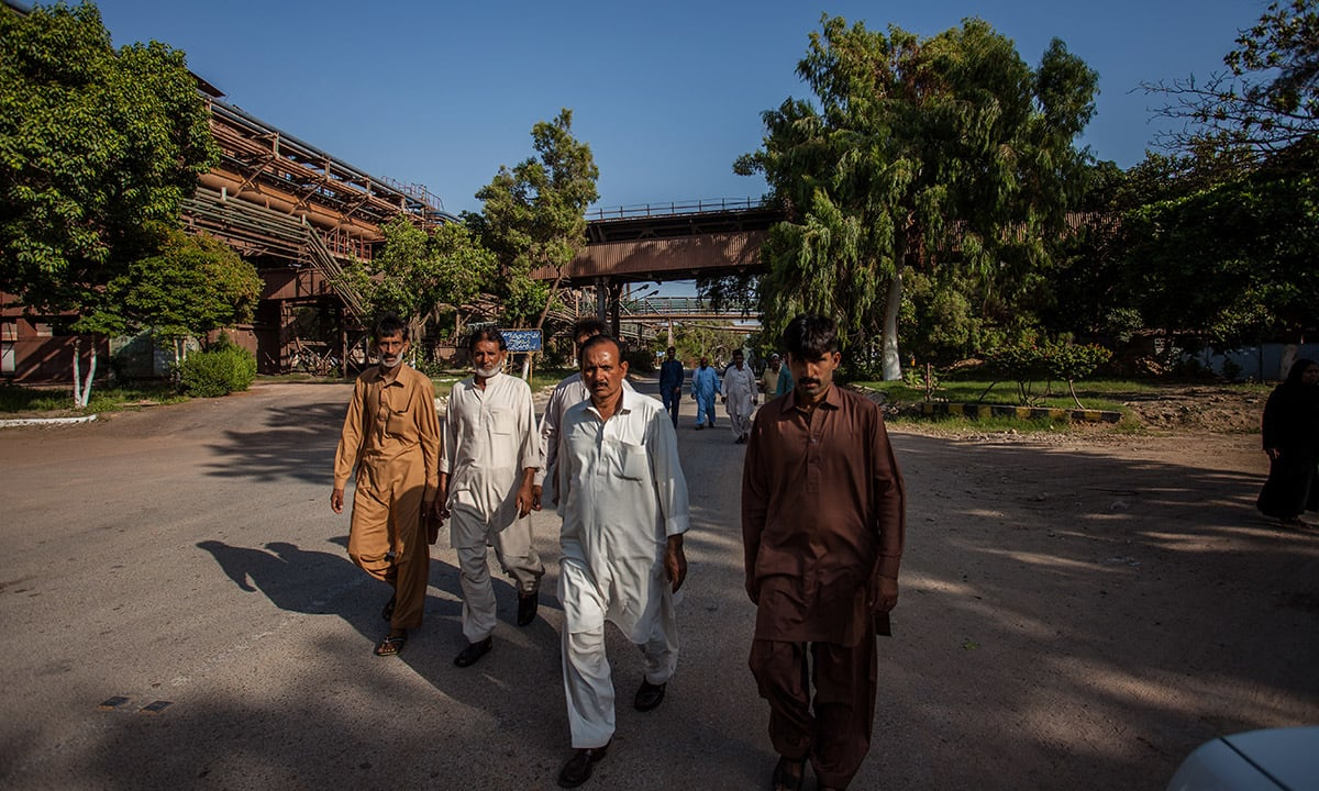 Pakistan Steel Mills workers head home after their day shift