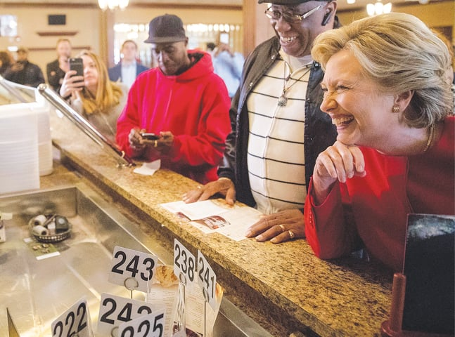 CLEVELAND: Democratic presidential candidate Hillary Clinton laughs as she orders lunch at a cafe on Monday.—AP