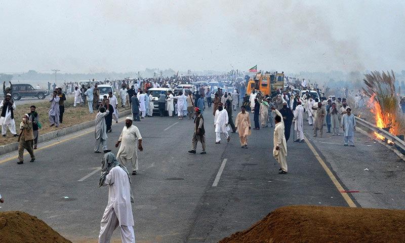 پولیس کی جانب سے آنسو گیس کی شیلنگ سے بچنے کے لیے مظاہرین نے جھاڑیوں میں آگ بھی لگائی— فوٹو / اے ایف پی
