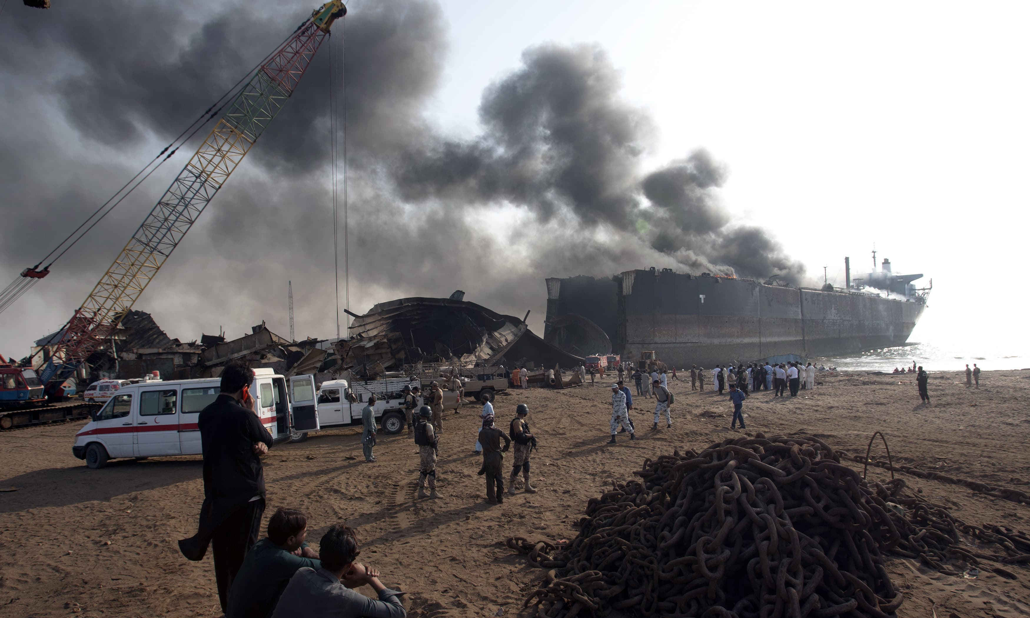 People look at a ship on fire following an explosion in Gadani. —AP