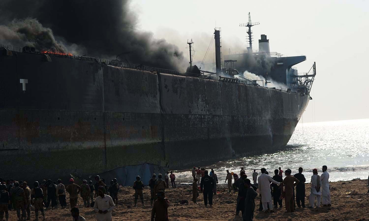Bystanders gather around the wreckage of a burning ship. ─AFP