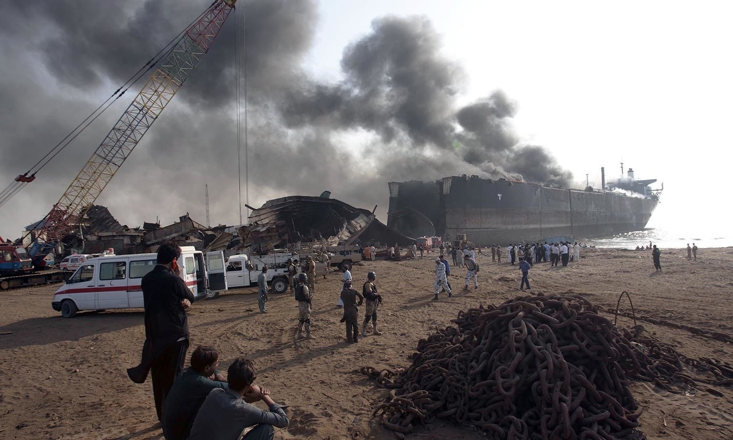 People look at the ship on fire following an explosion in the coastal town of Gadani. ─AP