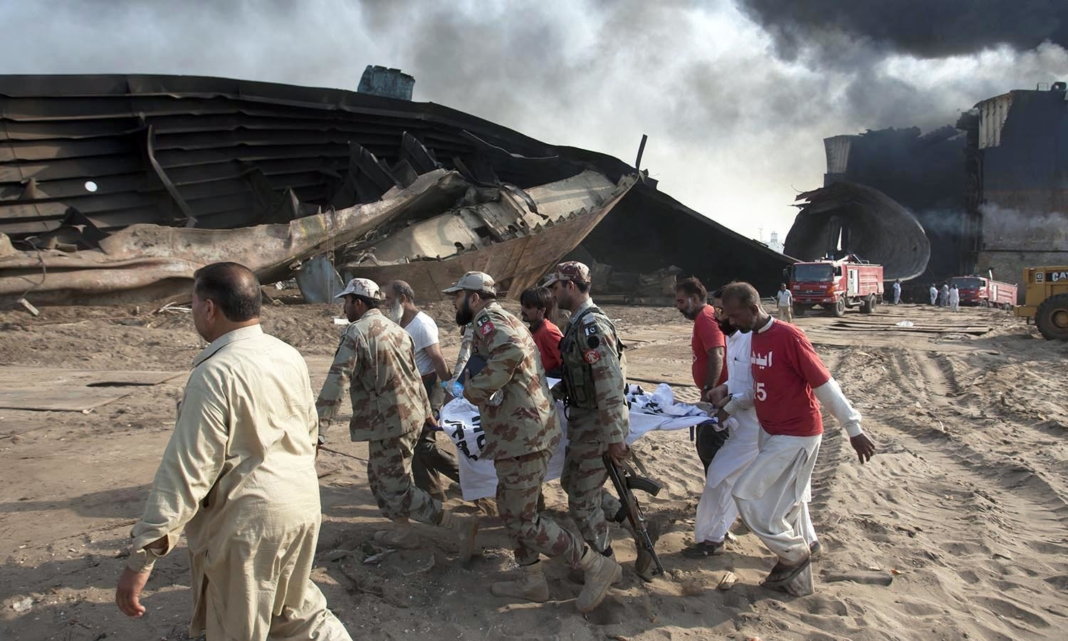 Security officials carry a body following an explosion and  fire on a ship, in the coastal town of Gadani.─AP