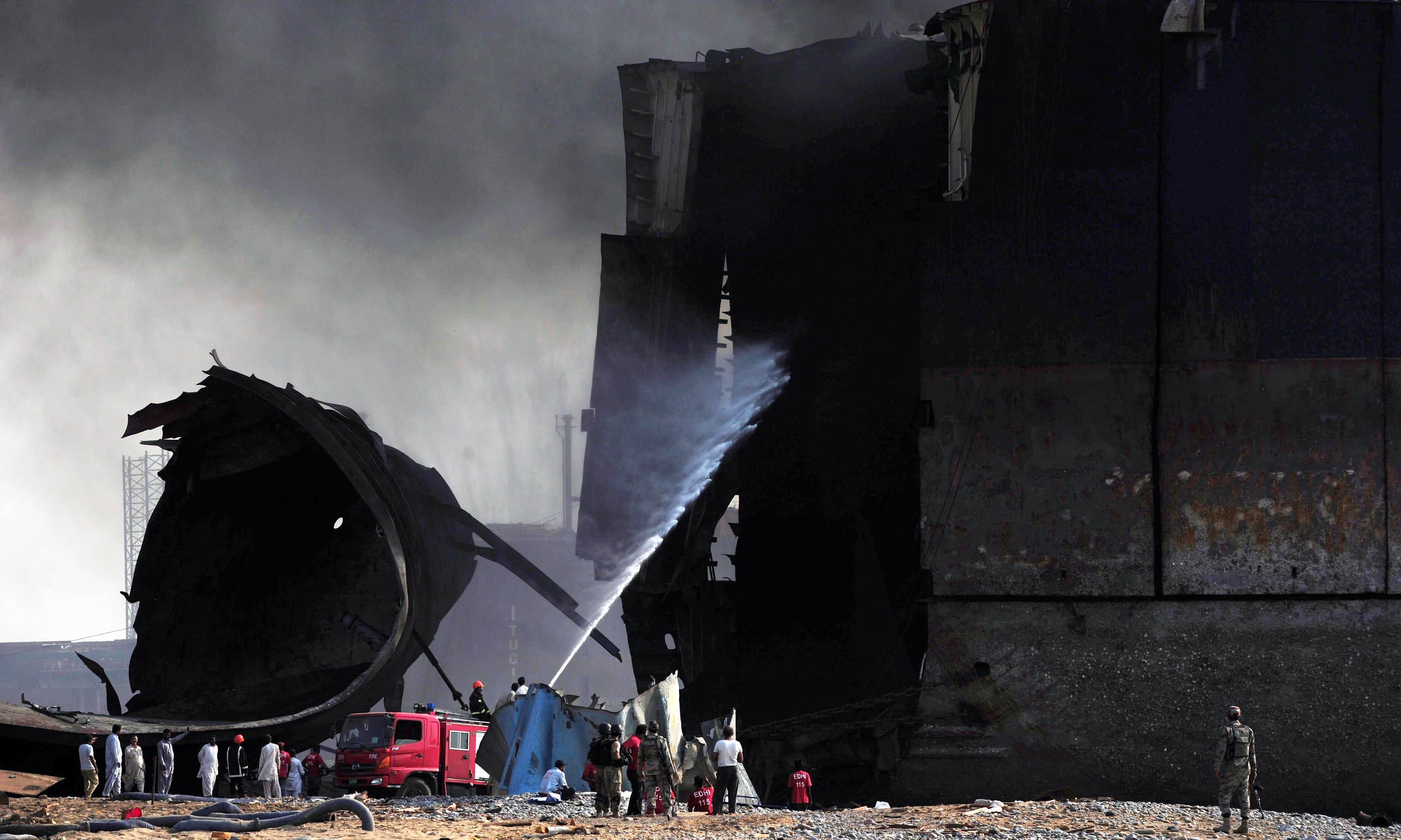 Firefighters use a hose as they attempt to extinguish a fire on a ship after a gas cylinder explosion at the Gadani shipbreaking yard. —AFP