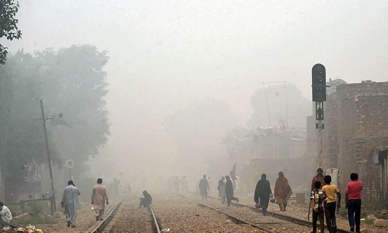 People walk along railway tracks during a smoggy day in Lahore.─AFP