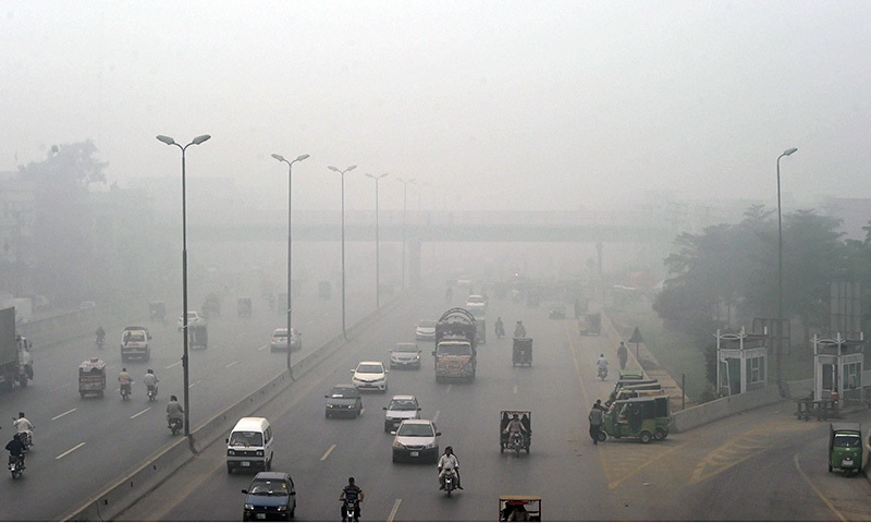 Commuters are seen on a street during a smoggy day in Lahore. ─AFP